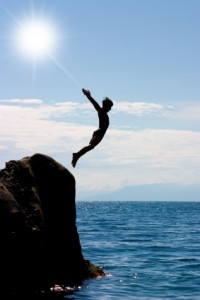 Boy jumping off a cliff